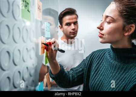 Intelligent coworking people preparing business strategy and posted on a sticky glass note wall. Smiling manager team brainstorming on new business id - Stock Photo