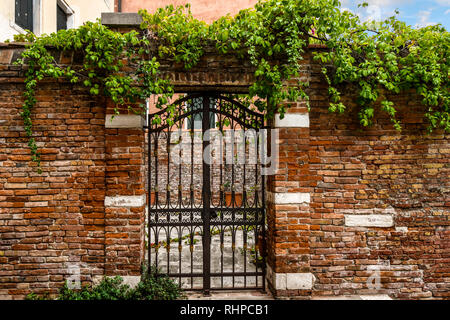 A wrought iron gate and brick wall in front of a medieval courtyard in the historic center of Venice, Italy - Stock Photo