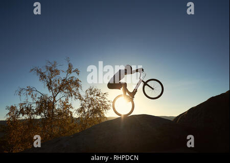 Silhouette of cyclist riding on back wheel on trial bike. Strong sportsman rider balancing on the edge of big rock on the top of mountain at sunset. Concept of extreme sport active lifestyle - Stock Photo