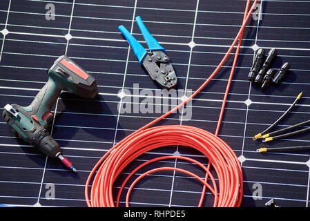 Close-up view of different details and instruments for installing and connecting solar photovoltaic system. Objects laying on blue solar panel