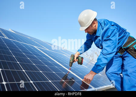 Man worker in blue suit and protective helmet installing solar photovoltaic panel system using screwdriver. Professional electrician mounting blue solar module. Alternative energy ecological concept. - Stock Photo