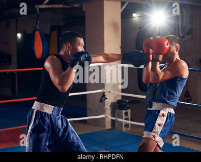 Two male angry fighters practicing kick boxing in the ring at the health club - Stock Photo