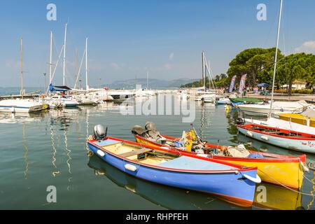 LAZISE, LAKE GARDA, ITALY - SEPTEMBER 2018: Colourful boats in the harbour in Lazise on Lake Garda. - Stock Photo