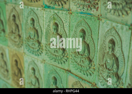 The wall in the temple is filled with buddhas. Religion Buddhism concept. Texture, background Buddhism