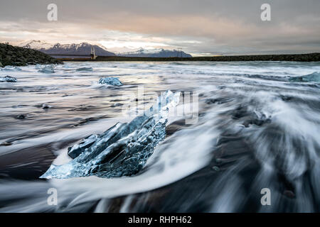 The stunningly beautiful Diamond Beach. Located The  by Jökulsárlón glacial lagoon in southeast Iceland. Chunks of iceberg wash up on this black lava  - Stock Photo