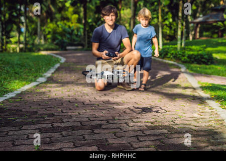 Dad and son playing with drone, man and boy playing with flying drone in sunny autumn garden, happy young boy and father playing with unmanned aerial - Stock Photo