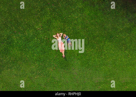 Mom and son are lying on the grass in the park, photos from the drone, quadracopter - Stock Photo