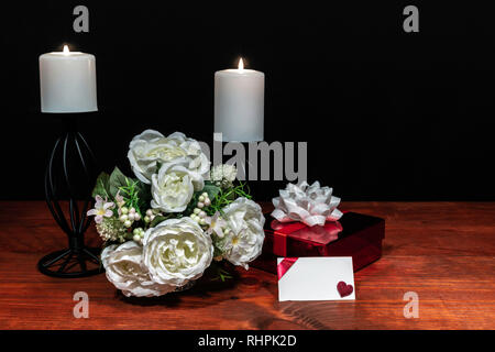 Beautiful bouquet of arranged flowers white candles on a holder with a present and a card on a wooden table. mothers day, Easter, valentines, birthday - Stock Photo