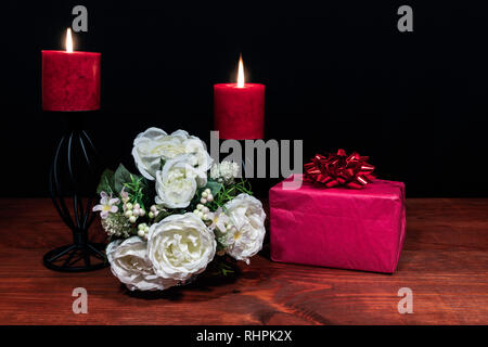 Beautiful bouquet of arranged flowers red candles on a holder with a present on a wooden table. mothers day, Easter, valentines, birthday, Christmas, - Stock Photo