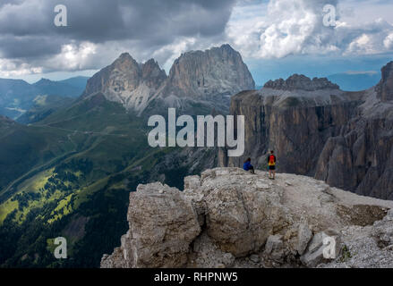 Two hikers taking a rest on top of Sass Pordoi in the Italian Dolomite mountains - Stock Photo