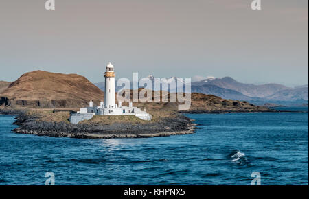 View on the old Eilean Musdile lighthouse in Scotland, with snowcapped highland peaks in the background - Stock Photo