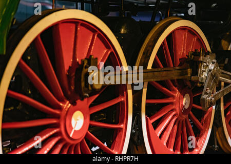 Bright red wheels of old locomotive on railway tracks closeup. Absract vintage background - Stock Photo
