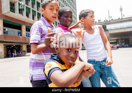 Caracas, Dtto Capital / Venezuela  04/04/2012 .Street boys in one of the most famous square in downtown Caracas.Behind them El Silencio towers. - Stock Photo