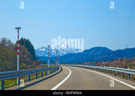 View of countryside road with Japan Alps mountain in the background. - Stock Photo