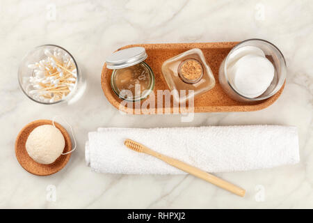 Sustainable toiletries, shot from the top. Homemade lotions, cotton pads, bamboo toothbrush, natural Konjac sponge, and biodegradable bamboo cotton - Stock Photo