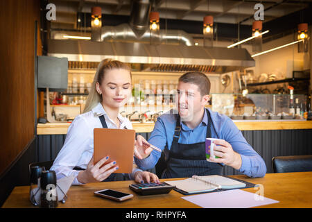 Young man and woman going through paperwork together in their restaurant. Small family restaurant owners discussing finance calculating bills - Stock Photo