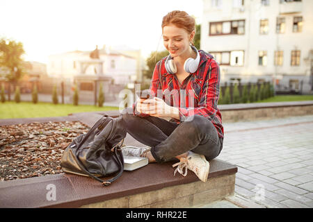 portrait of a young redhead female student in a checkered shirt. The girl listens to music in headphones. Looks at your mobile phone texting a message - Stock Photo