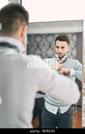 Handsome young man adjusting a tie in front of the mirror. Shopping, fashion, style and people concept - Stock Photo