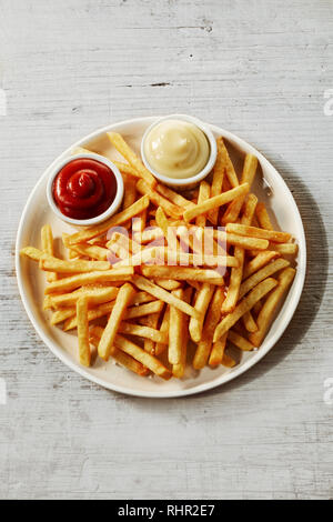 Plate of french fries potatoes served with ketchup and mayonnaise sauces in small bowls, viewed from above isolated on grey wooden background - Stock Photo
