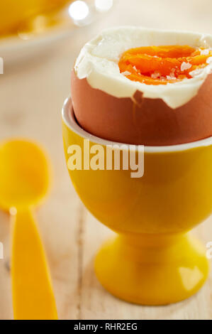 Close-up on open soft-boiled organic egg in yellow ceramic eggcup served with plastic spoon - Stock Photo