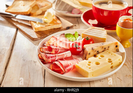 Variety of cheese and bacon served for sandwiches on white plate, with fresh tomatoes, toasts, boiled egg and cup of coffee - Stock Photo