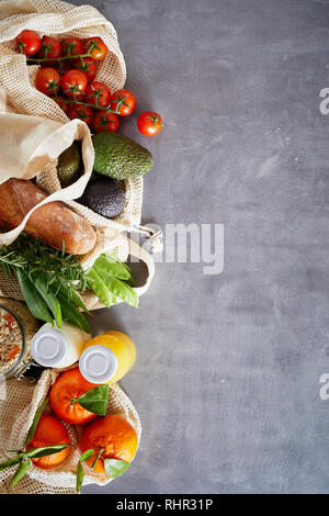 Fresh organic vegetables and fruits in fabric bags and glass bottles, viewed from above. Plastic free eco-friendly environmental shopping concept with - Stock Photo