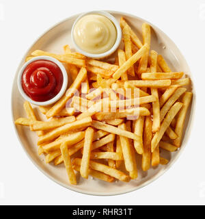 Plate of french fries potatoes served with ketchup and mayonnaise sauces in small bowls, viewed from above isolated on white background - Stock Photo