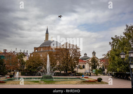 SOFIA, BULGARIA - OCTOBER 14, 2018: Many people enjoy sprinkling water of fountains in Banski Square in the Bulgarian capital. Moody cloudy sky autumn day. View from the staircase of History Museum - Stock Photo