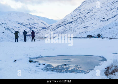 Photographers taking photos of snow covered mountains of the Three Sisters from the viewpoint off A82 at Glencoe, Highlands, Scotland in winter - Stock Photo