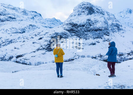 Tourists looking at the snow covered mountains of the Three Sisters  from the viewpoint off A82 at Glencoe, Highlands, Scotland in winter - Stock Photo