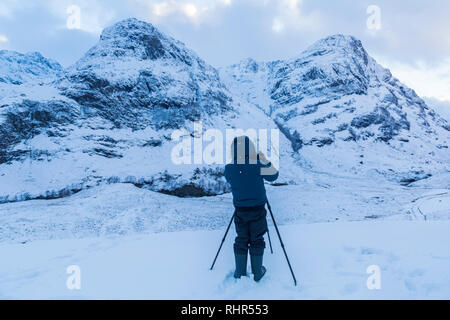 Photographer taking photos of snow covered mountains of the Three Sisters from the viewpoint off A82 at Glencoe, Highlands, Scotland in winter - Stock Photo