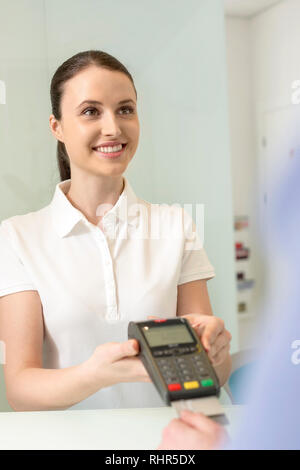 Smiling young woman making payment through credit card at checkout counter in clinic - Stock Photo
