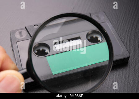 Audio cassette with space for text entry seen through magnifying glass. Cassette without description. Dark background. - Stock Photo