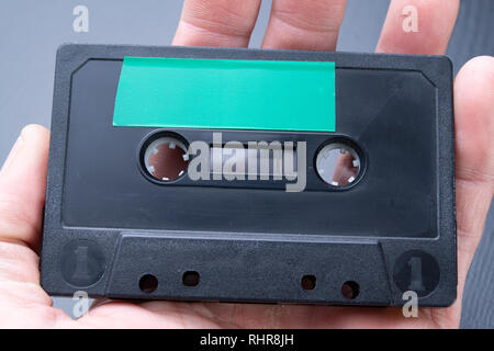 Audio cassette with space for text entry on the palm of your hand. Cassette without description. Dark background. - Stock Photo