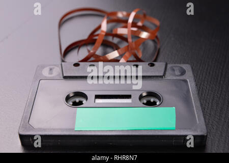 Audio cassette with space for text entry. Cassette without description. Dark background. - Stock Photo