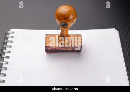Old wooden rubber stamp on a white piece of notebook. Office accessories on a dark table. - Stock Photo