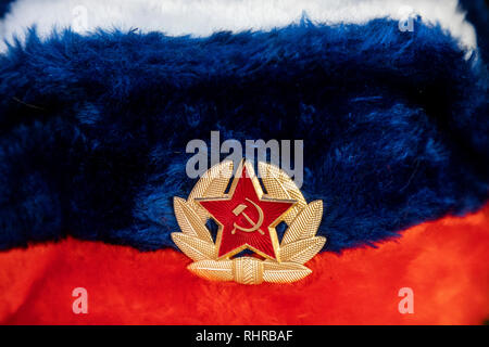 Earflaps fur cap with red soviet star in a souvenir shop in Moscow, Russia - Stock Photo