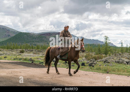 Mongolian man riding a horse in White Lake National Park. Tariat district, North Hangay province, Mongolia. - Stock Photo