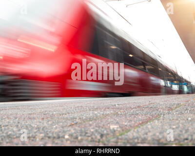 rail platform with red commuter train in motion blur in Cologne, Germany. - Stock Photo