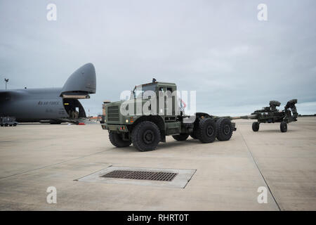 NAVAL STATION ROTA, Spain (Jan. 29, 2019) Equipment Operator 3rd Class Donovan Reyes, assigned to Naval Mobile Construction Battalion (NMCB) 1, operates a Medium Tactical Vehicle Replacement to tow a U.S. Army M777 howitzer from a U.S. Air Force C5M Super Galaxy during an embarkation operation. NMCB-1 is forward deployed to execute construction, humanitarian and foreign assistance, and theater security cooperation in the U.S. 6th Fleet area of operations. (U.S. Navy photo by Mass Communication Specialist 1st Class Caine Storino/Released) - Stock Photo