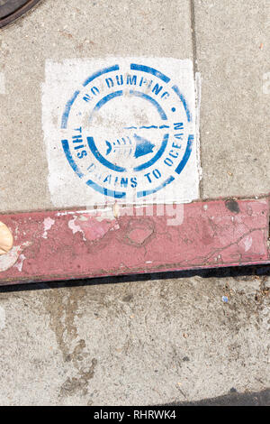 Sign above storm drain in Los Angeles, California which says 'No Dumping. This drains to ocean.' - Stock Photo