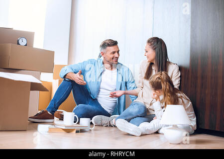 happy man sitting on floor and talking with wife near daughter - Stock Photo