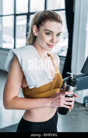 beautiful smiling young sportswoman with towel on shoulder holding sports bottle in gym - Stock Photo