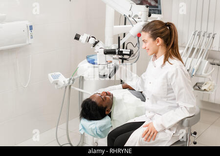 Female dentist advanced user, dental tools. Looking into the lens of a microscope while examining his patients teeth. in dental clinic office - Stock Photo
