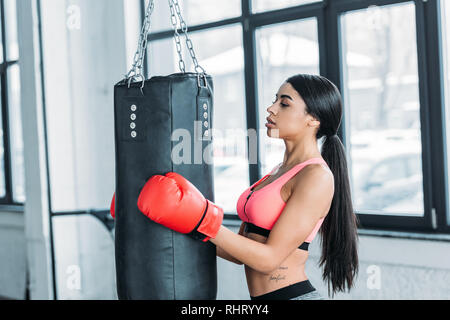 side view of young african american sportswoman in boxing gloves holding punching bag in gym - Stock Photo