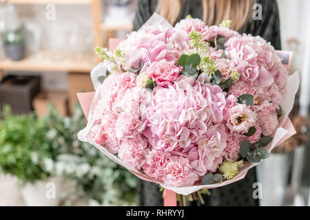 beautiful fresh cut bouquet of mixed flowers in woman hand. the work of the florist at a flower shop. Delicate Pastel tones color - Stock Photo