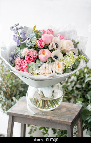beautiful fresh cut bouquet of mixed flowers in vase on wooden table. The work of the florist at a flower shop. Delicate Pastel tones color - Stock Photo
