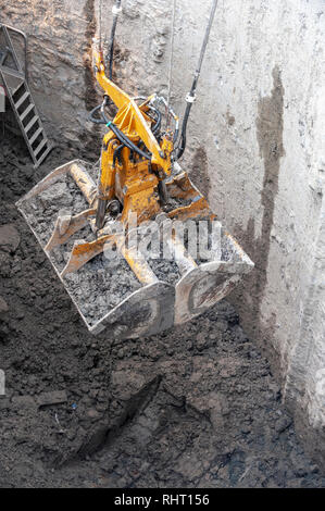 Construction site. A Dredge clamshell, rises a full bucket of muddy earth. - Stock Photo
