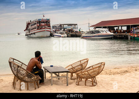 Cambodia, Preah Sihanoukh, Sihanoukhville, Occheuteal Beach, jetty, man at empty beach bar watching tourists depart on boats to offshore islands - Stock Photo