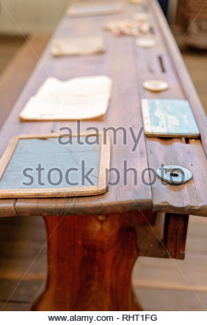 Vintage wooden student form desk with inkwell and slate as used in a school room in yesteryear - Stock Photo